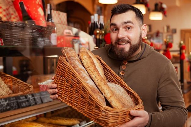 Jonge, bebaarde man lacht, mand vol verschillende brood te houden.