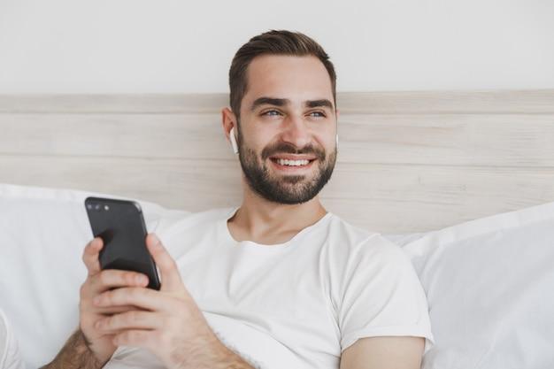 Jonge, bebaarde man liggend in bed met witte laken kussen deken in slaapkamer thuis at