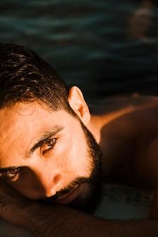 Jonge, bebaarde man liggend op het water
