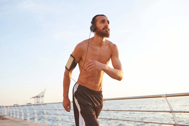 Jonge, bebaarde man loopt aan zee, luistert naar favoriete liedjes op de koptelefoon, geniet van de ochtend en het leven.
