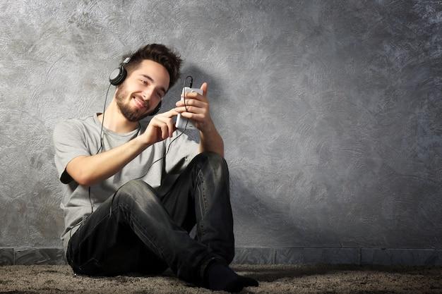 Jonge, bebaarde man luisteren muziek met koptelefoon op grijze muur