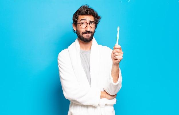 Jonge, bebaarde man met badjas en tandenborstel
