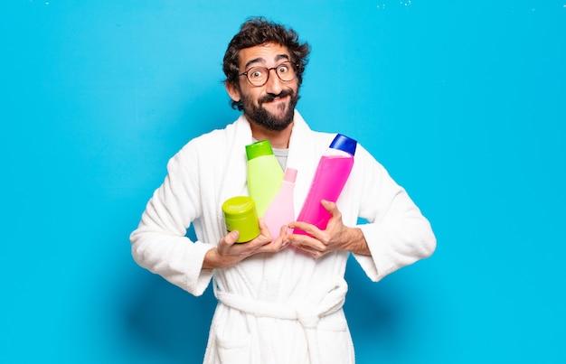 Jonge, bebaarde man met badjas met shampoo en schoonheidsproducten