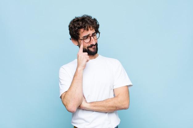 Jonge, bebaarde man met bril op blauwe muur
