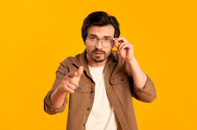 Jonge, bebaarde man met bril toont een vinger, zegt