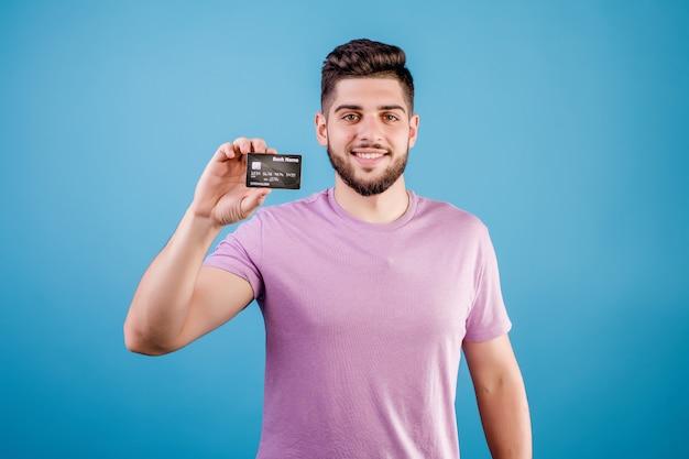 Jonge, bebaarde man met creditcard geïsoleerd op blauw