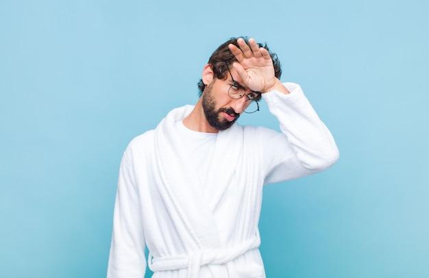 Jonge, bebaarde man met een badjas die er gestrest, moe en gefrustreerd uitziet, het zweet van het voorhoofd droogt, zich hopeloos en uitgeput voelt