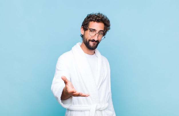 Jonge, bebaarde man met een badjas die glimlacht, er gelukkig, zelfverzekerd en vriendelijk uitziet, een handdruk aanbiedt om een deal te sluiten, samenwerkt