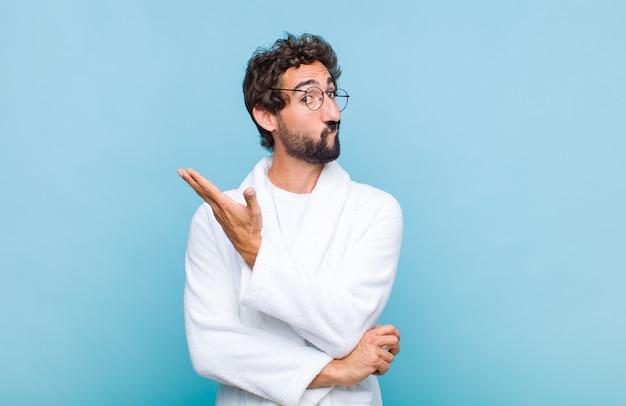Jonge, bebaarde man met een badjas die zich verward en onwetend voelde en zich afvroeg over een twijfelachtige verklaring of gedachte
