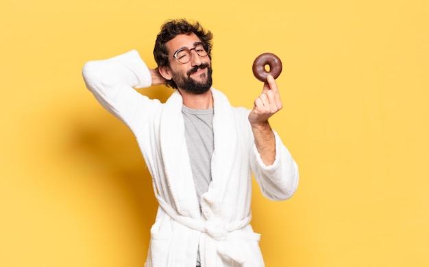 Jonge, bebaarde man met een badjas met een chocolade donut