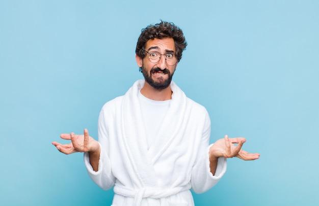 Jonge, bebaarde man met een badjas voelt zich geen idee en verward, niet zeker welke keuze of optie hij moet kiezen, zich afvragend