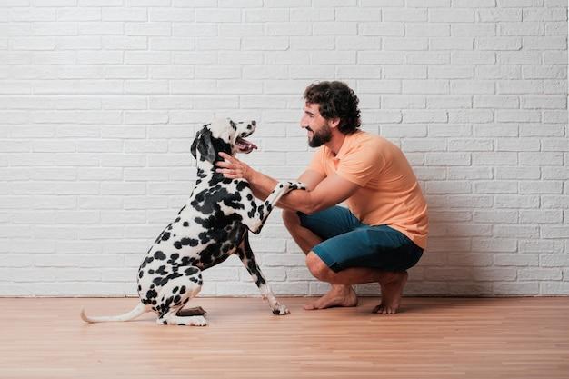Jonge, bebaarde man met een dalmatische hond tegen witte bakstenen muur