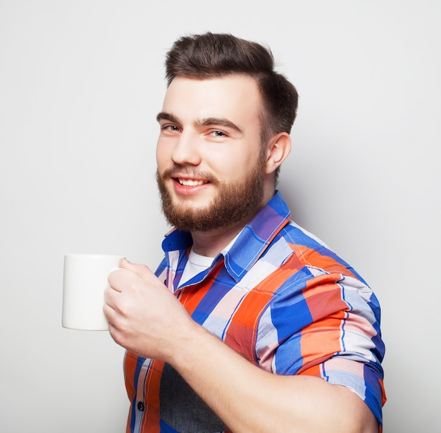 Jonge, bebaarde man met een kopje koffie