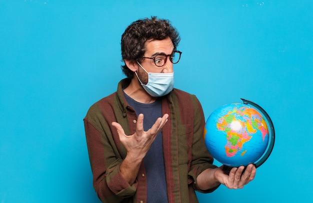 Jonge, bebaarde man met een medisch masker en een wereldkaartmodel