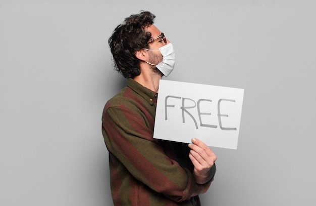 Jonge, bebaarde man met een medisch masker en gratis bord