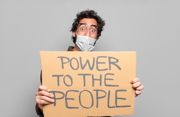 Jonge, bebaarde man met een medisch masker met power to the people concept