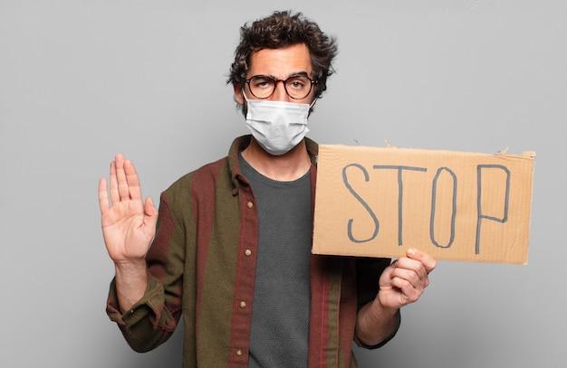 Jonge, bebaarde man met een medisch masker stop concept