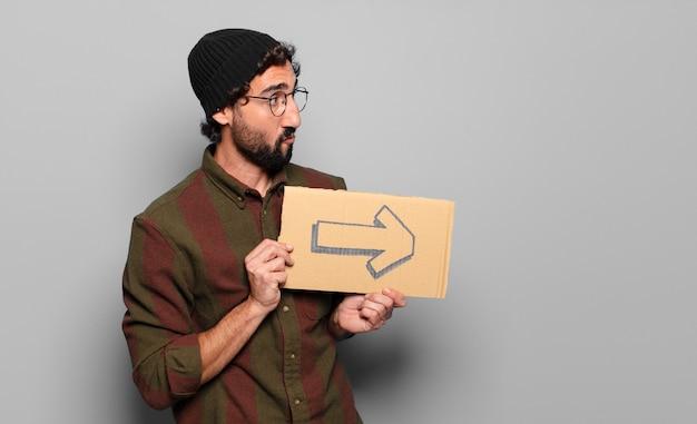 Jonge, bebaarde man met een pijlsymbool op karton
