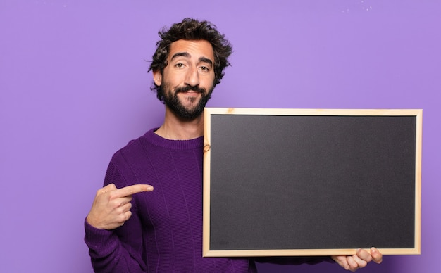 Jonge, bebaarde man met een schoolbord