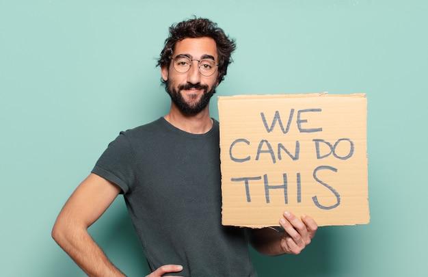 Jonge, bebaarde man met kartonnen stuk met we kunnen deze inscriptie doen