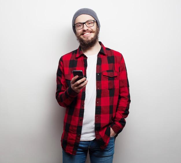 Jonge, bebaarde man met mobiele telefoon