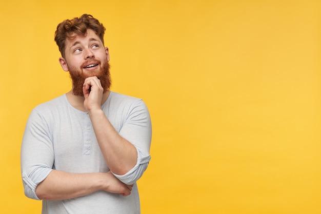 Jonge, bebaarde man met rood haar, draagt een leeg t-shirt, kijkt bedachtzaam en gelukkig opzij naar de kopie ruimte en raakt zijn kin op geel.