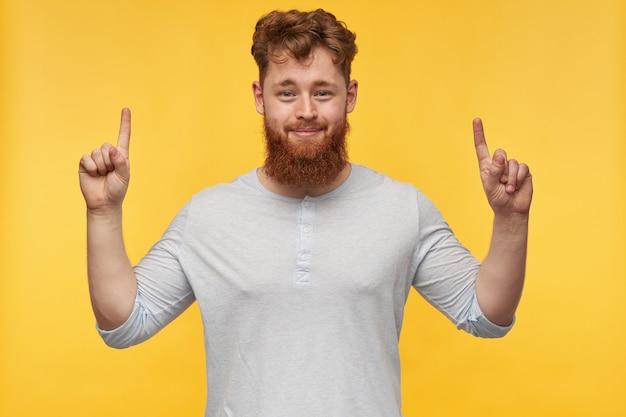 Jonge, bebaarde man met rood haar, voelt zich gelukkig en glimlachend wijst met de vingers naar boven op kopie ruimte op geel.
