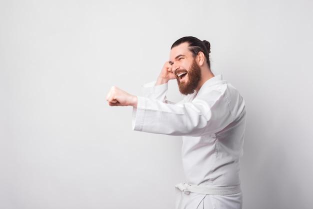 Jonge, bebaarde man met taekwondo uniform ponsen over witte muur