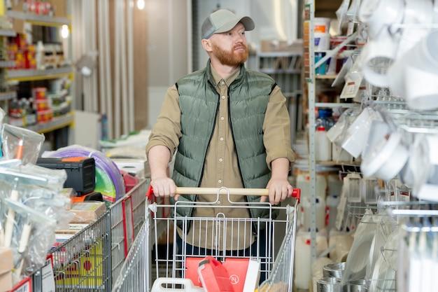 Jonge, bebaarde man met winkelwagen die ijzerwinkel bezoekt