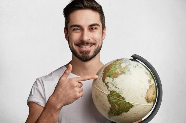 Jonge, bebaarde man met wit t-shirt en globe