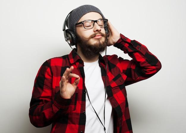 Jonge bebaarde man muziek beluisteren
