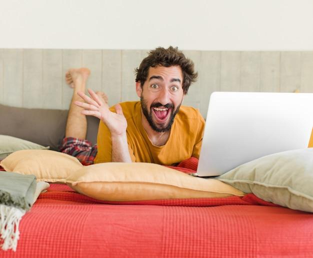 Jonge, bebaarde man op een bed met een laptop