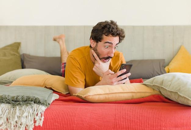 Jonge, bebaarde man op een bed met zijn mobiele telefoon