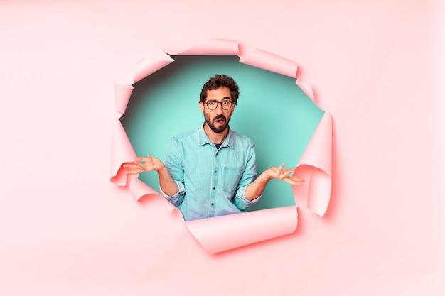 Jonge, bebaarde man op roze papieren gat