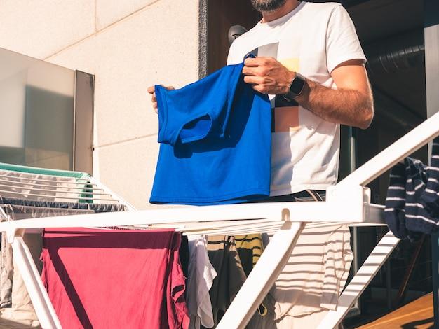 Jonge, bebaarde man opknoping blauw t-shirt op het terras van zijn loft