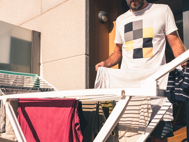 Jonge, bebaarde man opknoping wit t-shirt op het terras van zijn loft