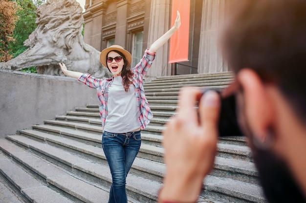 Jonge, bebaarde man praten foto van gelukkige vrouw. ze poseert op camera. de vrouwelijke toerist houdt handen omhoog en draagt glazen. ze staan op trappen.