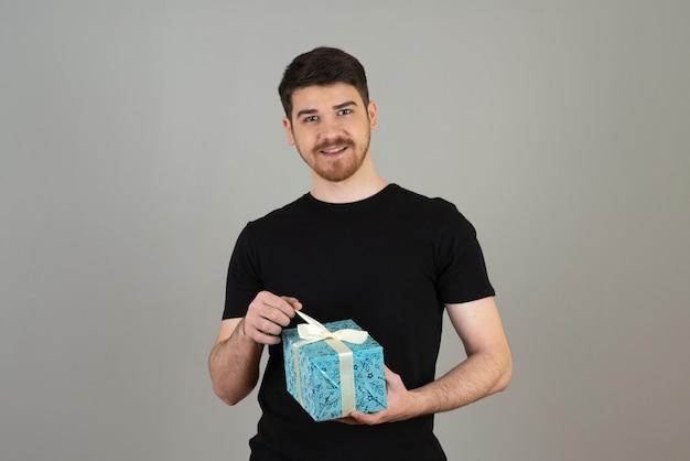 Jonge, bebaarde man probeert cadeau te openen op een grijze.