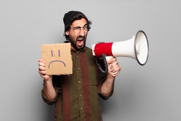 Jonge, bebaarde man protesteert met een megafoon