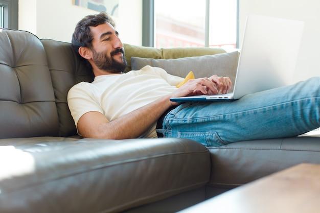 Jonge, bebaarde man rust op een bank met een laptop
