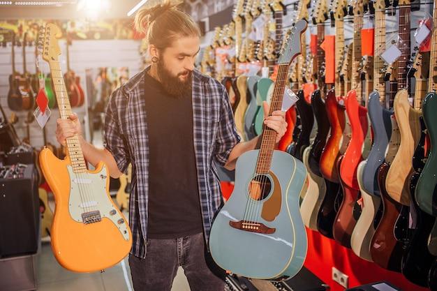 Jonge bebaarde man staan en houd elektrische en akoestische gitaren. hij kijkt naar de blauwe. jonge hipster alleen in kamer vol met gitaren en verschillende apparatuur.