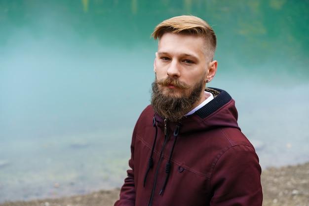 Jonge, bebaarde man stond alleen bij het meer en keek peinzend opzij rokende sigarettenmist over het w...