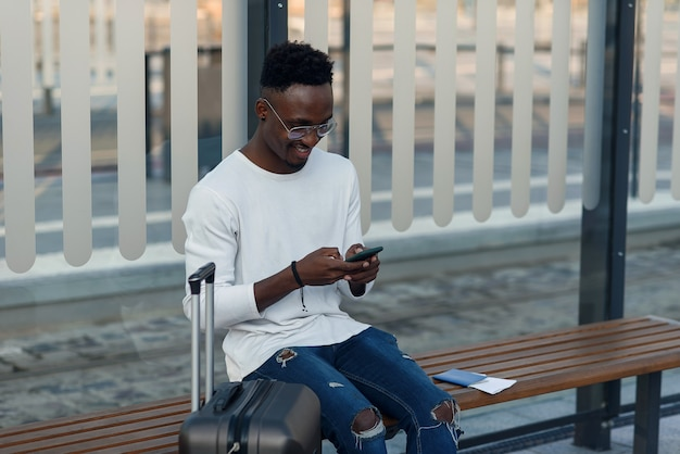 Jonge, bebaarde man toerist met rugzak en smartphone zit op de halte van het openbaar vervoer en wachten op tram in het centrum