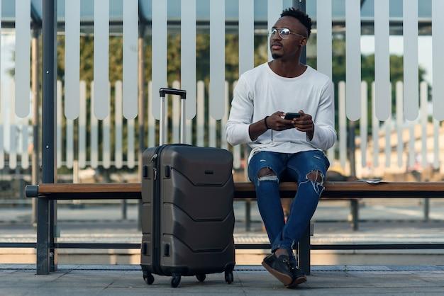 Jonge, bebaarde man toerist met rugzak en smartphone