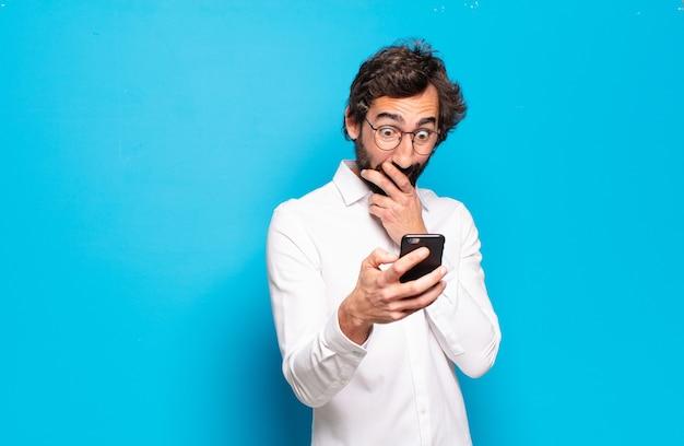 Jonge, bebaarde man toont zijn mobiele scherm