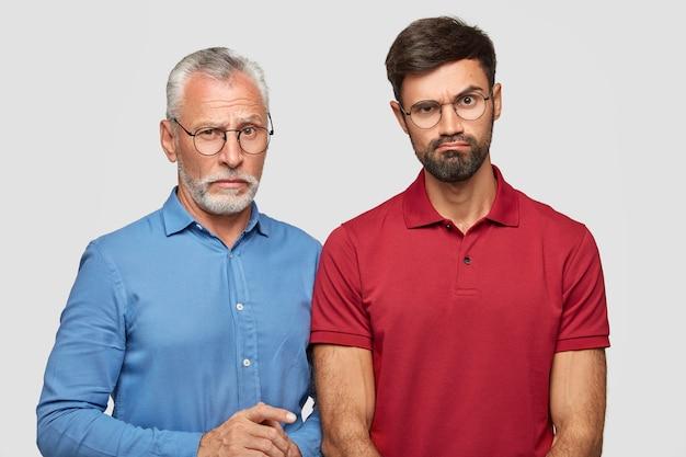 Jonge, bebaarde man trekt verbijsterd wenkbrauw op, gekleed in een rood t-shirt, staat naast zijn volwassen vader, brengt weekend door in familiekring, geïsoleerd over een witte muur. relatie concept