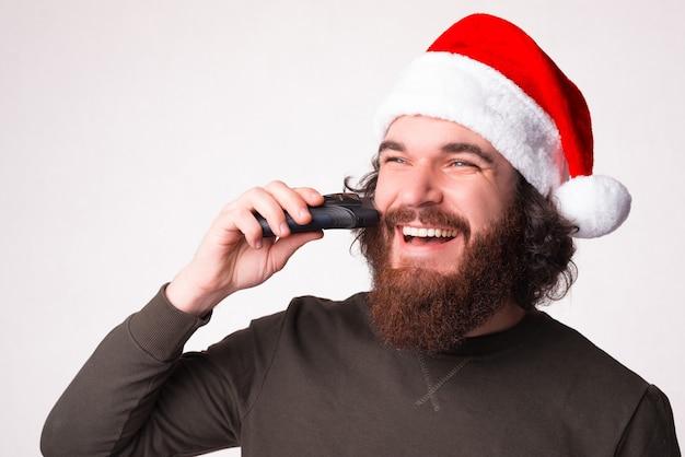 Jonge, bebaarde man trimt zichzelf terwijl hij een kerstmuts draagt.