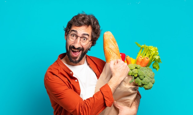 Jonge, bebaarde man voelt zich gelukkig, positief en succesvol, gemotiveerd wanneer hij voor een uitdaging staat of goede resultaten viert en een groentezak vasthoudt Premium Foto