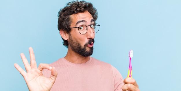 Jonge, bebaarde man voelt zich geschokt, verbaasd en verrast, toont goedkeuring en maakt goed teken met beide handen