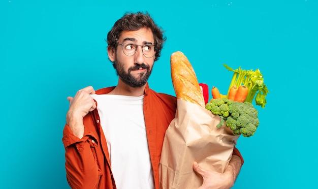 Jonge, bebaarde man voelt zich gestrest, angstig, moe en gefrustreerd, trekt de hals van het shirt aan, kijkt gefrustreerd door het probleem en houdt een zak met groenten vast
